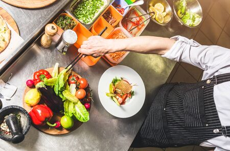 Professional chef cooking in the kitchen restaurant at the hotel, preparing dinner. A cook in an apron makes a salad of vegetables and pizza. 스톡 콘텐츠 - 129376648