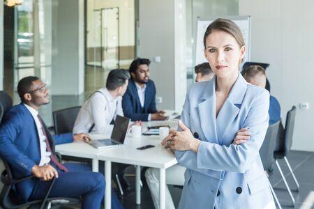 Business woman stands on the background of partners. A team of young businessmen working and communicating together in an office. Corporate businessteam and manager in a meeting