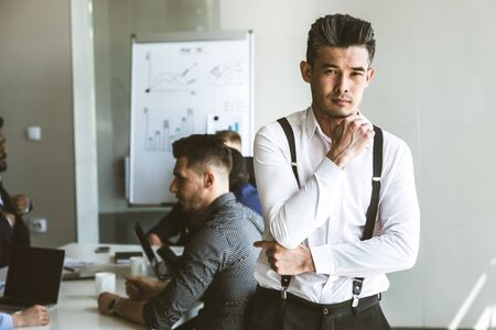 Business man stands on the background of partners. A team of young businessmen working and communicating together in an office. Corporate businessteam and manager in a meeting.
