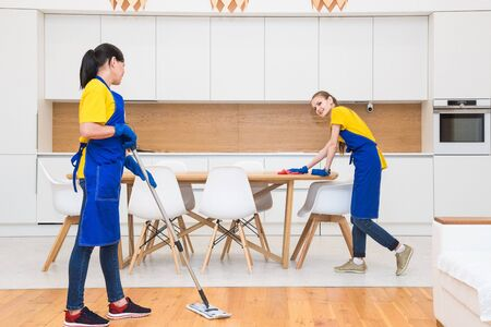 professional cleaning service. Two women in working uniform, in aprons, divide the cleaning of the kitchen of a private house, cottage. washing the refrigerator, tap, sink. Wash floor. 스톡 콘텐츠