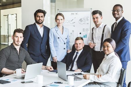 A team of young businessmen stand shoulder to shoulder, working and communicating together in an office. Corporate businessteam and manager in a meeting.