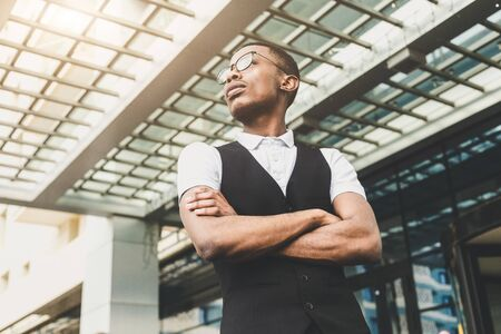 Young african american business man in suit and eyeglasses talking on the phone on the background of the business center 스톡 콘텐츠 - 129376658