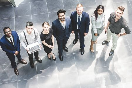 view from above. A team of young businessmen working and communicating together in an office. Corporate businessteam and manager in a meeting.