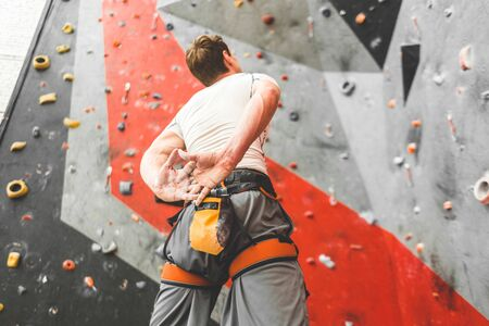 Sportsman climber is looking on steep rock, climbing on artificial wall indoors. Extreme sports and bouldering concept 스톡 콘텐츠 - 129376672