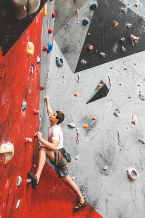 Sportsman climber moving up on steep rock, climbing on artificial wall indoors. Extreme sports and bouldering concept 스톡 콘텐츠 - 129376681