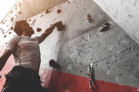 Sportsman climber moving up on steep rock, climbing on artificial wall indoors. Extreme sports and bouldering concept 스톡 콘텐츠