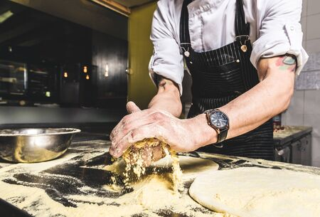 Professional chef cooking in the kitchen restaurant at the hotel, preparing dinner. A cook in an apron makes a salad of vegetables and pizza 스톡 콘텐츠 - 129376686
