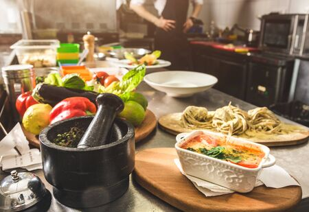 Professional chef cooking in the kitchen restaurant at the hotel, preparing dinner. A cook in an apron makes a salad of vegetables and pizza 스톡 콘텐츠 - 129376691