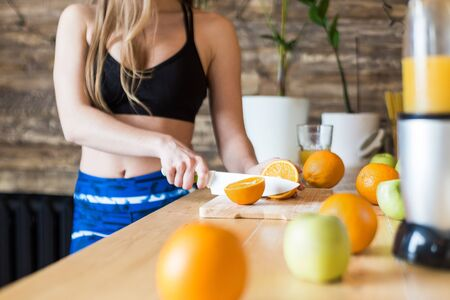 Attractive girl in sportswear preparing a healthy breakfast in the kitchen before training, cutting fruit and making fresh juice. Healthy lifestyle, fitness and beaut. 스톡 콘텐츠 - 129376695