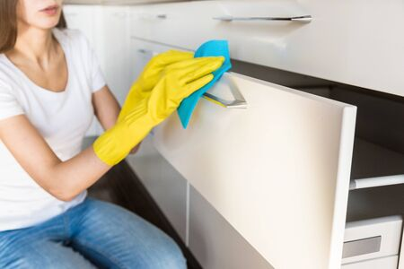 A young woman from a professional cleaning company cleans up at home. A man washes the kitchen in yellow gloves with cleaning supplies stuff