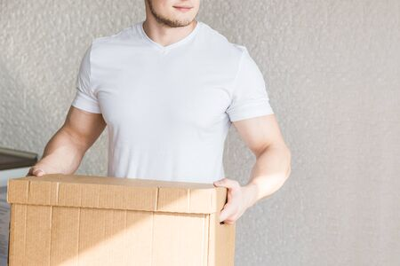 Delivery strong, muscular man loading cardboard boxes for moving to an apartment. professional worker of transportation, male loaders in overalls. free space for text, isolated.