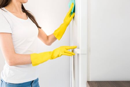 A young woman from a professional cleaning company cleans up at home. A man washes the kitchen washes the fridge in yellow gloves with cleaning supplies stuff