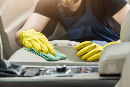 Cleaning service. Man in uniform and yellow gloves washes a car interior in a car wash. Worker washes the chairs of the leather salon.