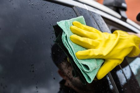Cleaning service. Man in uniform and yellow gloves washes a car glass window in a car wash.