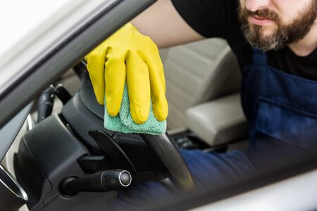 Cleaning service. Man in uniform and yellow gloves washes a car interior in a car wash.