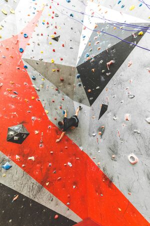 Sportsman climber moving up on steep rock, climbing on artificial wall indoors. Extreme sports and bouldering concept. 스톡 콘텐츠 - 129376636