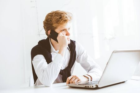 Young businessman working in the office at the laptop