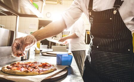 Professional chef cooking in the kitchen restaurant at the hotel, preparing dinner. A cook in an apron makes a salad of vegetables and pizza