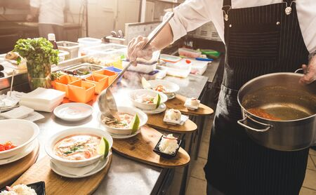 Professional chef cooking in the kitchen restaurant at the hotel, preparing dinner. A cook in an apron makes a salad of vegetables and pizza 스톡 콘텐츠 - 130955413