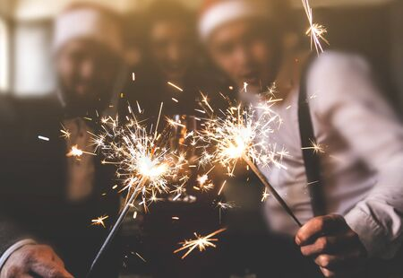 sparklers in the foreground. Beautiful young people at a corporate party. New Year celebration. Club party with friends