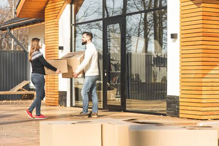 young couple moves to a new home. the family carries boxes of things after buying a home 스톡 콘텐츠 - 132370932