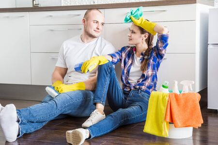 Young couple husband and wife do the house cleaning. The guy and the girl wash the kitchen with a mop and cloth, teamwork, fun Imagens - 142516043