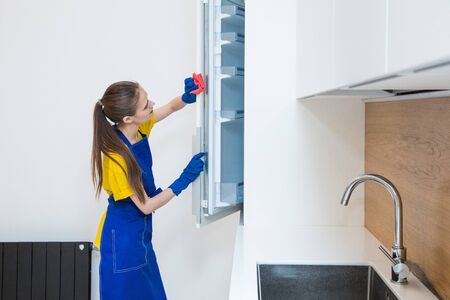 professional cleaning service. Two women in working uniform, in aprons, divide the cleaning of the kitchen of a private house, cottage. washing the refrigerator, tap, sink. Wash floor.