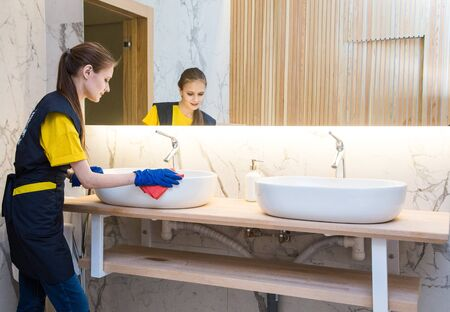 professional cleaning service. woman in uniform and gloves sponge washes the plumbing in the bathroom. Washing bath and sink Reklamní fotografie