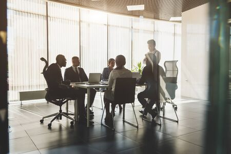 Silhouettes of people sitting at the table. A team of young businessmen working and communicating together in an office. Corporate businessteam and manager in a meeting. Archivio Fotografico