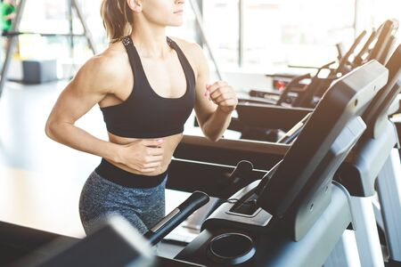 The athletic woman dressed in a black sportswear running on the treadmill in the modern gym. Stock Photo