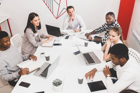 A team of young office workers, businessmen with laptop working at the table, communicating together in an office. Corporate businessteam and manager in a meeting. coworking
