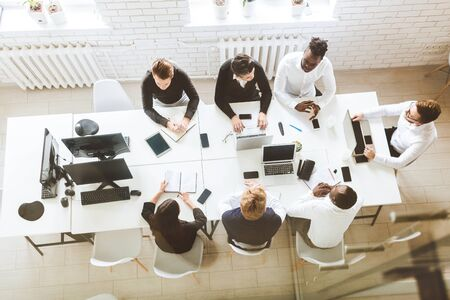 A team of young businessmen sitting at the table, top view, working and communicating together in an office. Corporate businessteam and manager in a meeting Foto de archivo