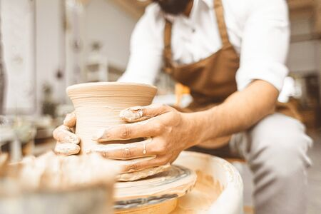 A young male potter works in his workshop on a potter's wheel and makes clay products. Close-up of hands.