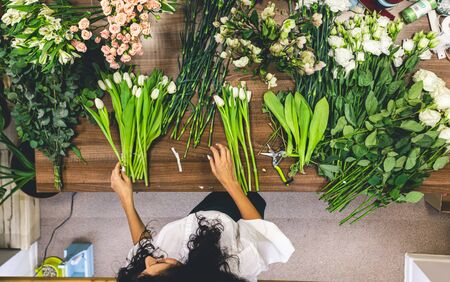 Flower shop. A woman seller sorts and collects bouquets of many fresh flowers. Top view on counter Imagens