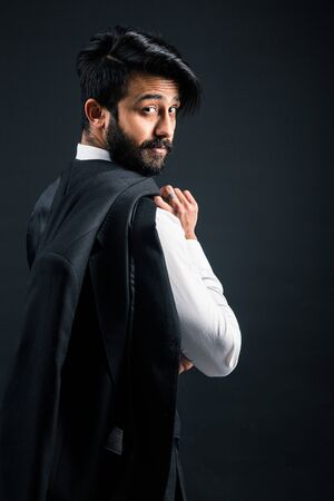 Portrait of a young handsome successful Indian in a classic black three-piece business suit on a dark background, Holding his jacket over his shoulder Stock Photo