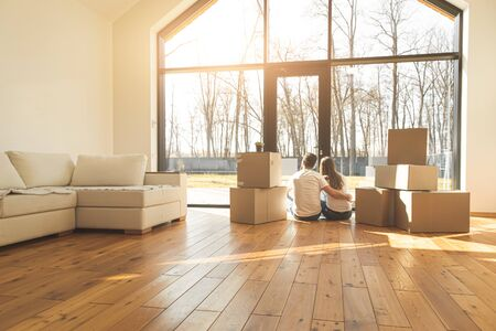young couple moves to a new home. the family carries boxes of things after buying a home