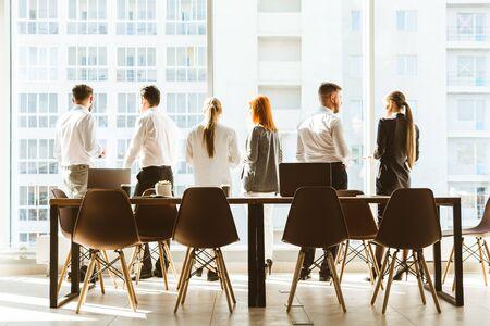 Zespół młodych biznesmenów pracujących i komunikujących się razem w biurze. Zespół korporacyjny i menedżer na spotkaniu. pulpit na tle okna panoramowania, wolne miejsce na tekst