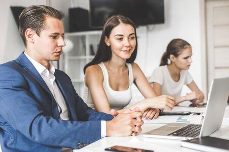 Une équipe de jeunes employés de bureau, des hommes d'affaires avec un ordinateur portable travaillant à table, communiquant ensemble dans un bureau. Équipe d'entreprise et gestionnaire lors d'une réunion. cotravail.