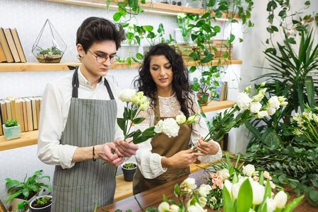 Attractive experienced female florist teaches a young man how to work in a flower shop