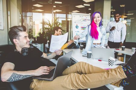 Group of multi ethnic executives discussing during a meeting. Business man and woman sitting around table at office and smiling. A team of young creative designers