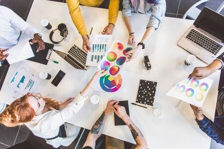 Gruppe von multiethnischen Führungskräften, die während eines Meetings diskutieren. Business-Mann und Frau sitzen am Tisch im Büro und lächeln. Ein Team junger kreativer Designer. Standard-Bild