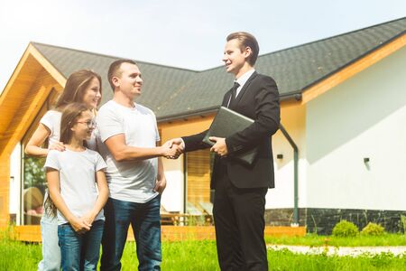 real estate agent is selling an apartment to a young family. conclusion of a lease and purchase of a house, apartment. man shows housing Reklamní fotografie