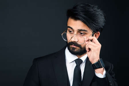 Portrait of a young handsome successful Indian in a classic black three-piece business suit on a dark background, hold down the glasses