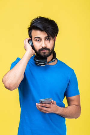 Emotional portrait of a Hindu man in a blue T-shirt on a yellow background
