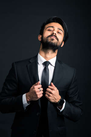 Portrait of a young handsome successful Indian in a classic black three-piece business suit on a dark background, holding with both hands the jacket lapels