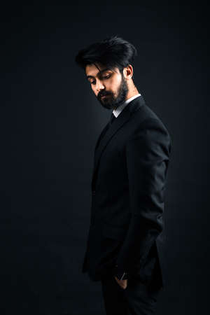 Portrait of a young handsome successful Indian in a classic black three-piece business suit on a dark background