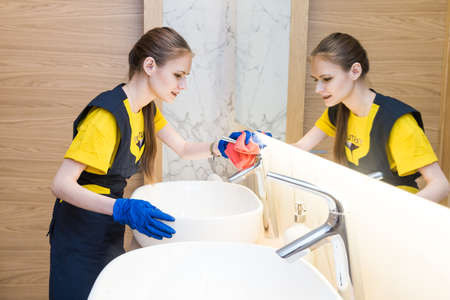 professional cleaning service. woman in uniform and gloves sponge washes the plumbing in the bathroom. Washing bath and sink Banque d'images - 150886254