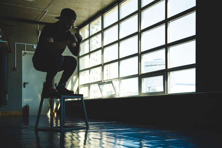 sports man jumps on a special platform in the gym opposite the window. Crossfit silhouette shot 写真素材