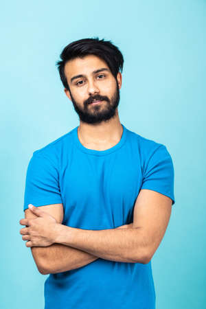 Emotional portrait of a handsome Hindu man in a blue T-shirt and arms crossed on a bright blue background