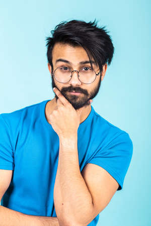 Emotional portrait of a handsome Hindu man in a blue T-shirt on a bright blue background, think about something 免版税图像